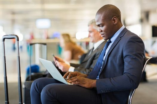 black CPA working at airport on computer